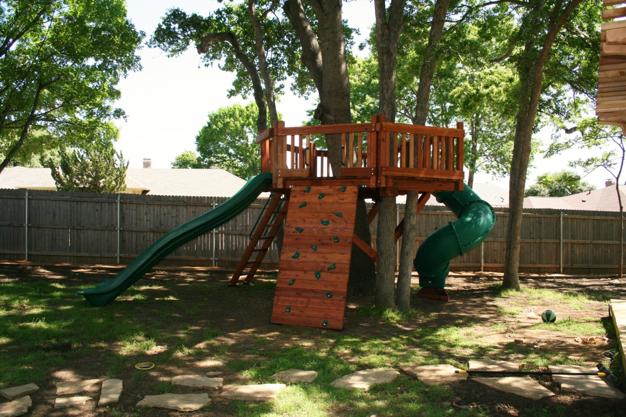 Tree deck with twister slide rock wall